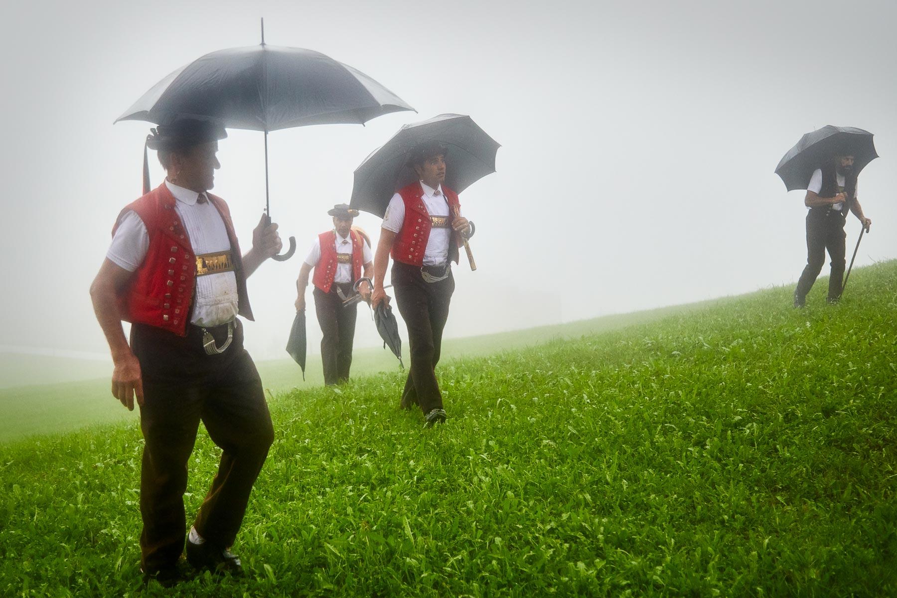Appenzeller Sennen im Regen mit Regenschirmen